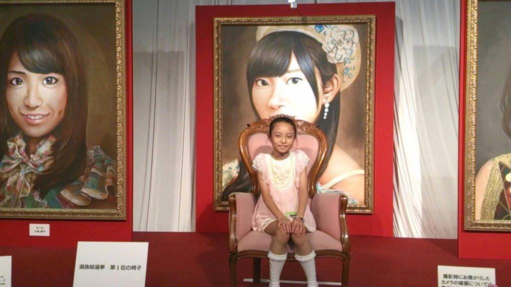 AKB48を応援しているえりさん親子。AKB48選抜総選挙にまつわるグッズが展示された『AKB48選抜総選挙ミュージアム』にて、指原莉乃さんの肖像画を前に娘さんが記念撮影。