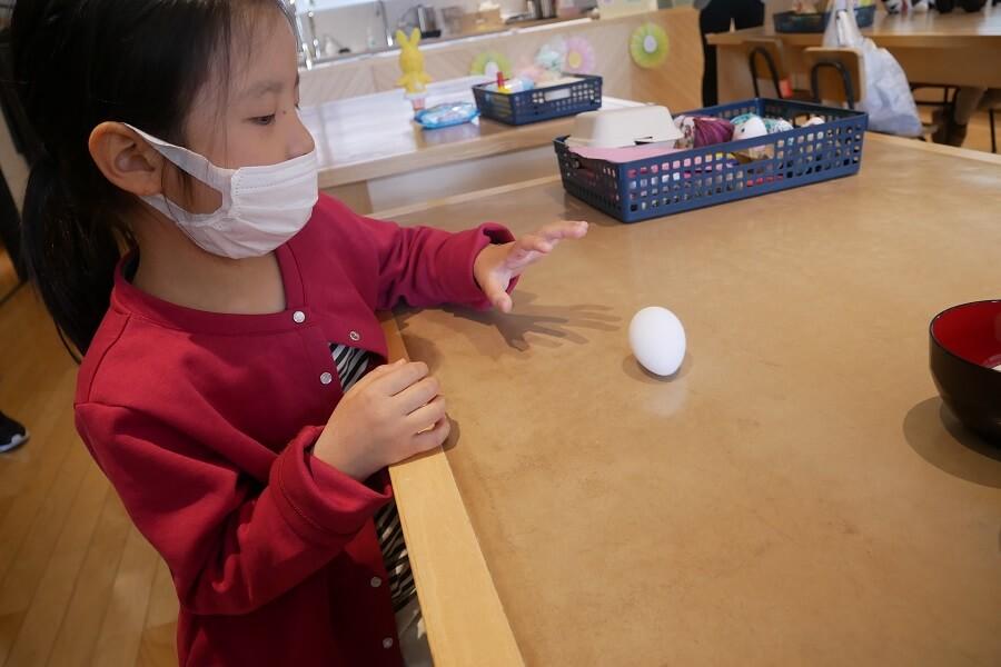 卵を転がすと、大きな円を描いて元の位置に戻ってくることに驚き、何度も転がす娘。