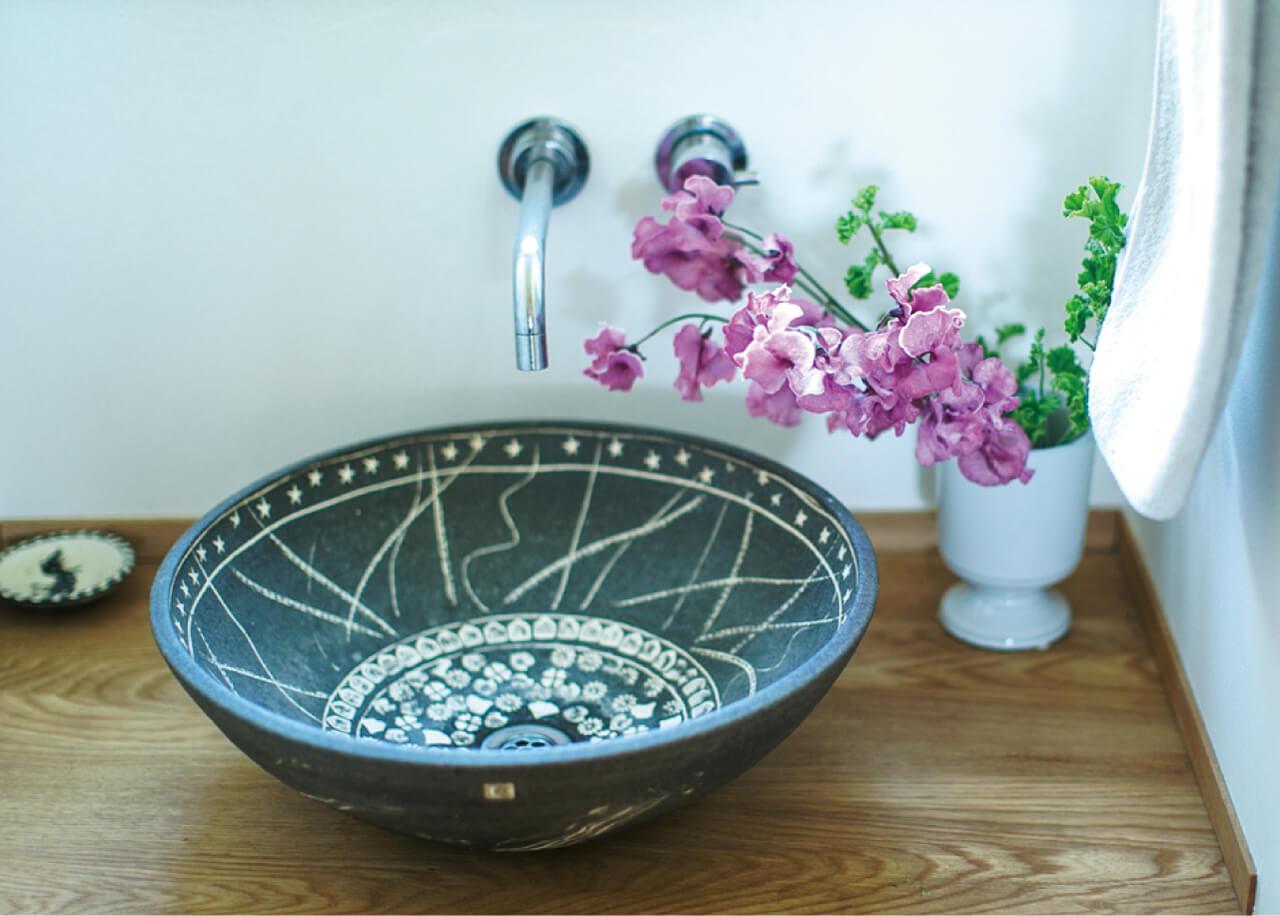 手洗いボウルは、家族で作陶した思い出の品。そのわきには香りのいいスイートピーとゼラニウムを。