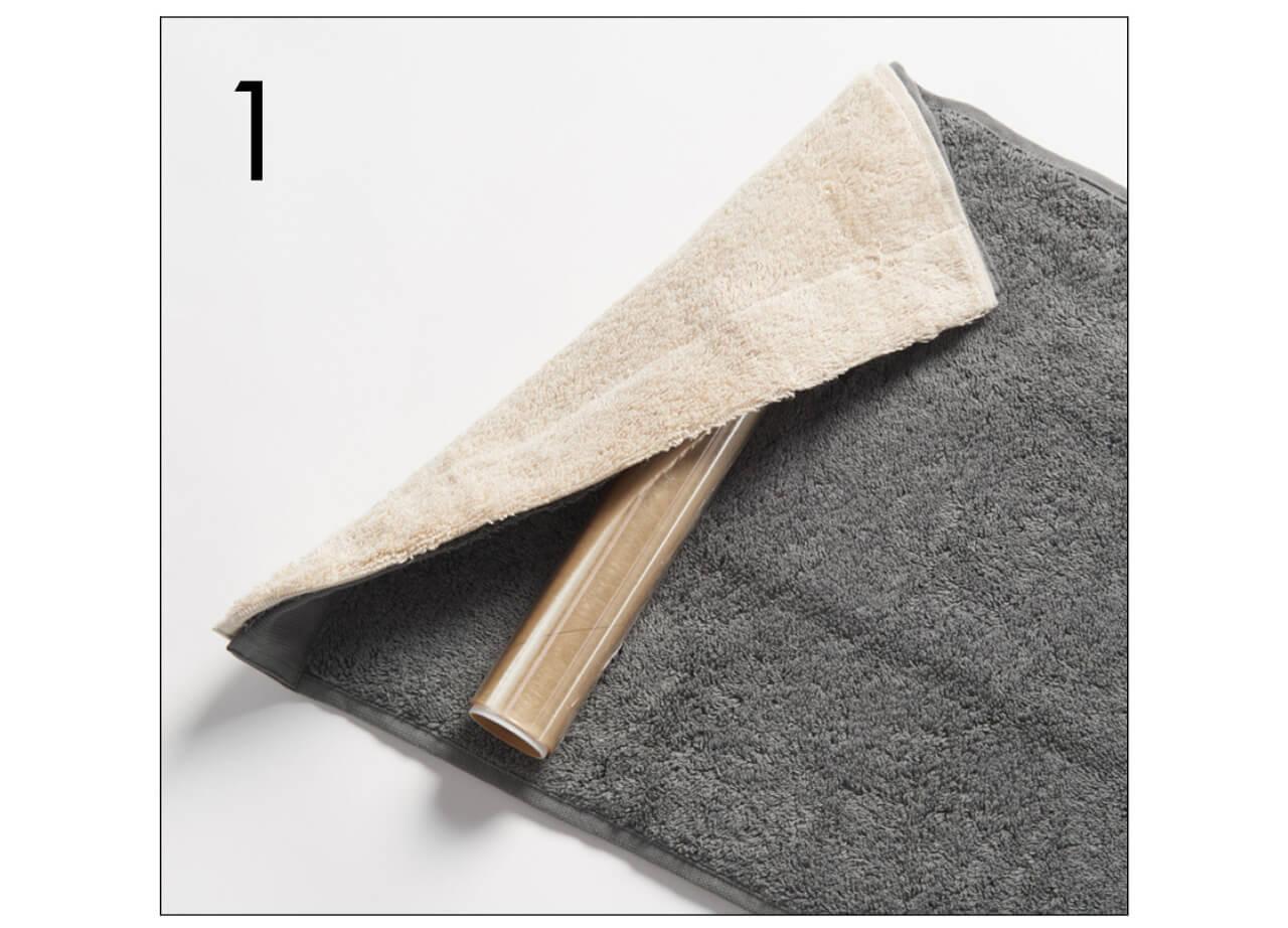 1.フェイスタオルを2枚重ね、ラップを芯にしてクルクルと巻いていく。