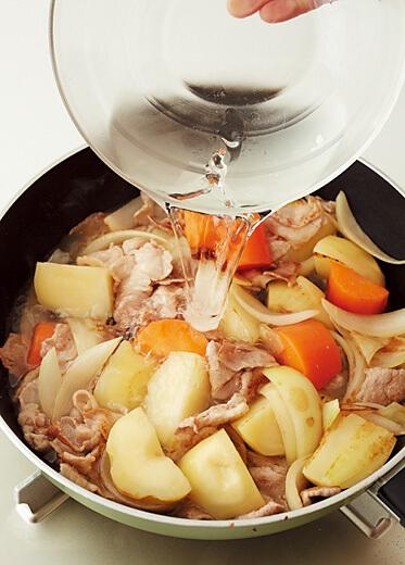 煮込むためにフライパンにフタをする写真:フライパンで「肉じゃが」レシピ/小林まさみさん