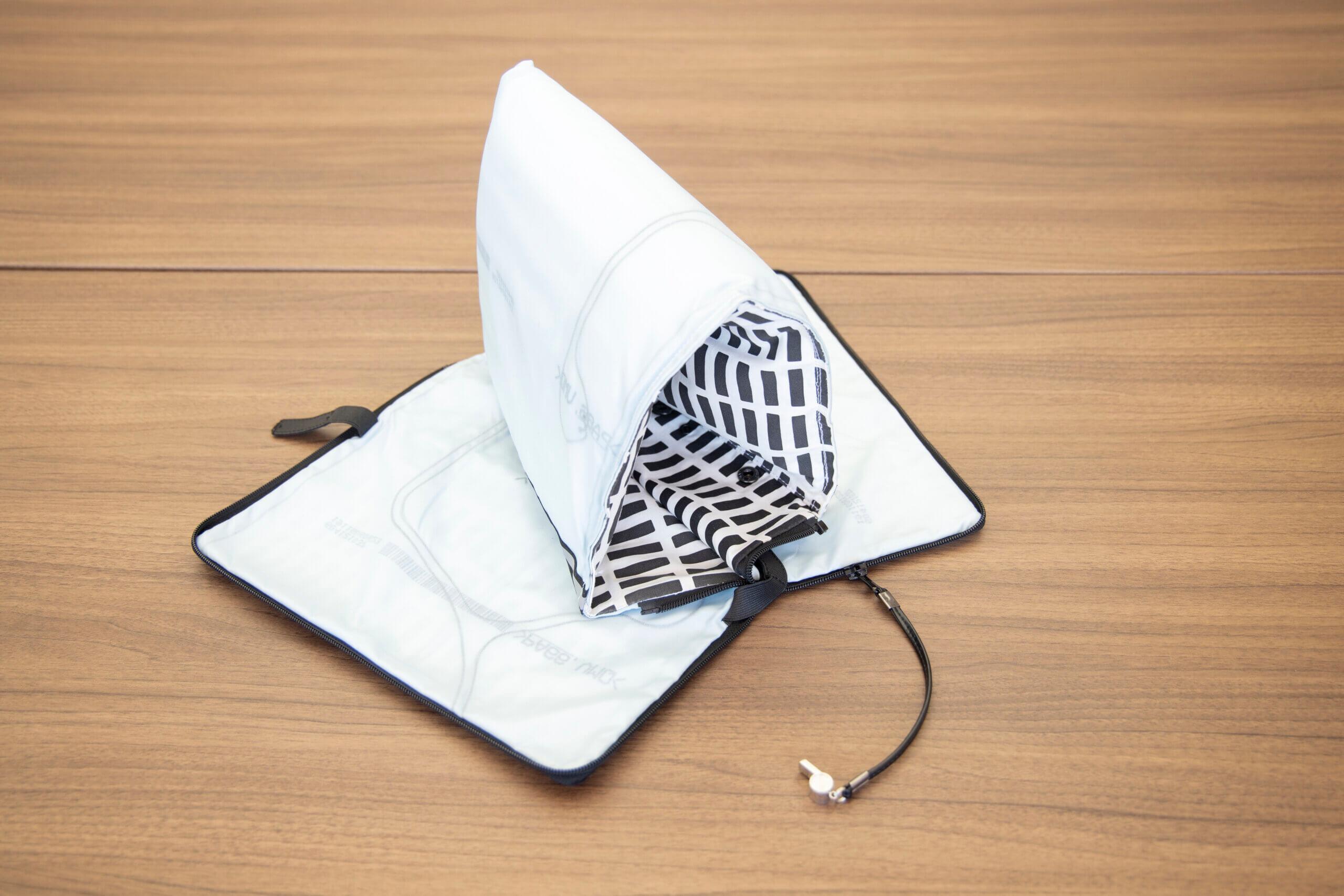 こちらは、トートバッグとセットになっているクラッチバッグ。モノトーンの格子柄のデザインがとてもおしゃれなんですが、なんと、空気を入れて膨らませると、防災頭巾に早変わり!