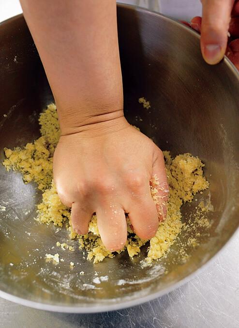 材料が入っているボウルに菜種油を加え手で混ぜている写真