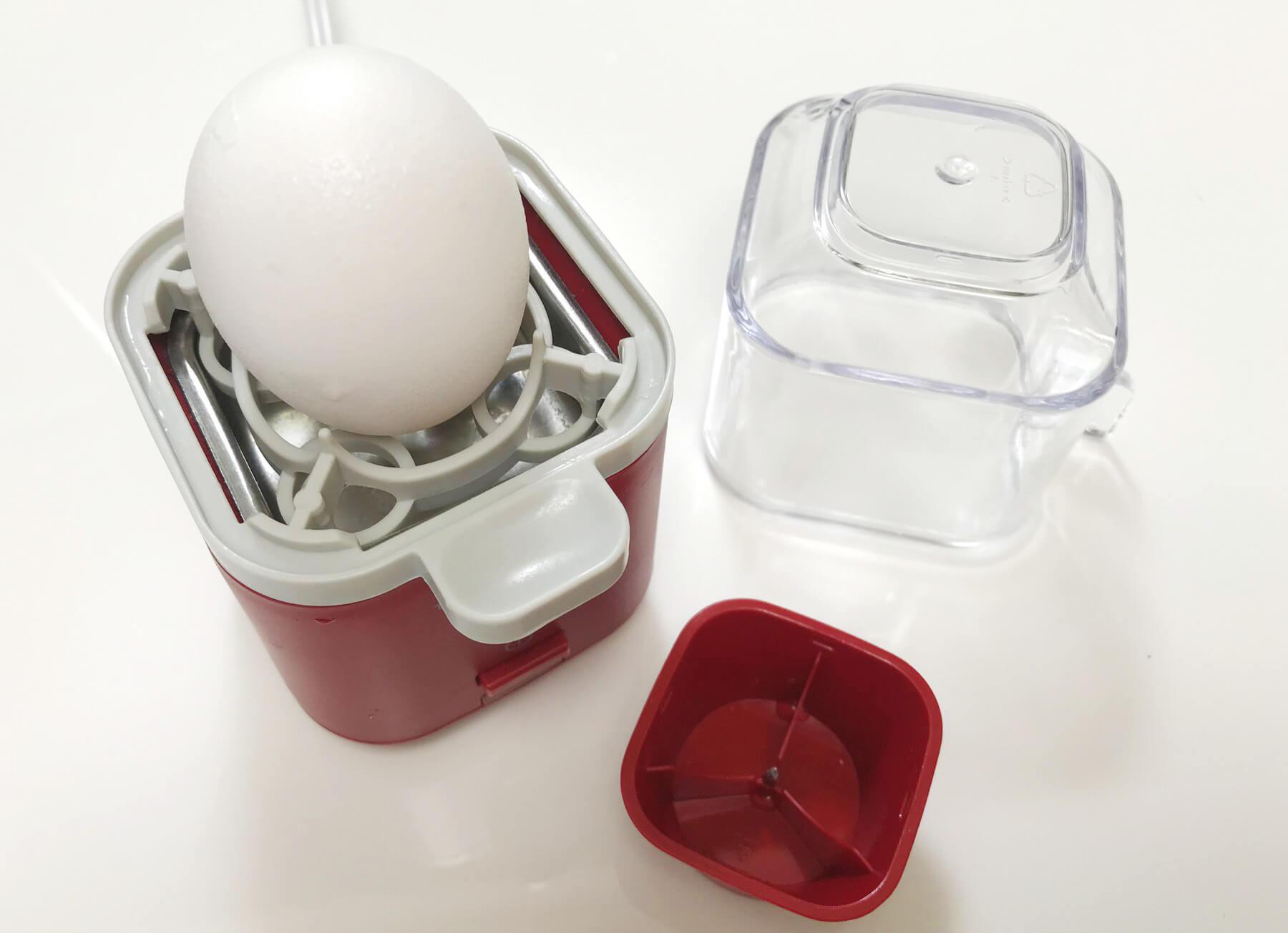 水を入れる本体のほか、卵をのせるリバーシブルトレイ、蒸気口のあるクリアカバー、赤い計量カップが付属しています
