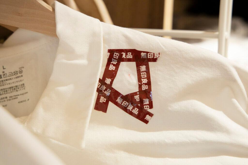"""こちらのシャツは、1点のシミがあるから割引き価格に。このようにどこが """"ワケあり""""なのかがわかりやすくて親切!納得してお得に買えるのがうれしい。"""